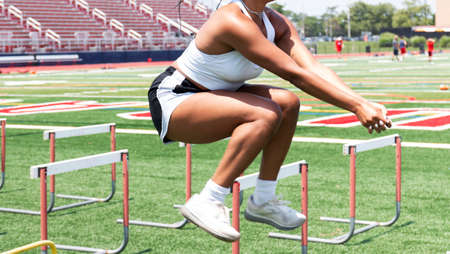 Side view of a young women working out jumping over track hurdles on a turf field for strength and agility.