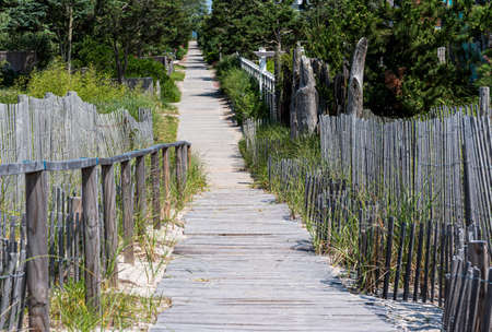 Walking over the sand dunes on a wooden path exiting the beach into the neighborhood of summer homes.