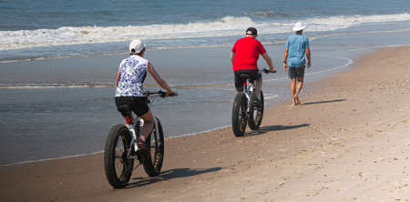 Rear view of a couple riding fat wheel bikes passing a walker on the waters edge at the beach on Fire Island New York. Stockfoto