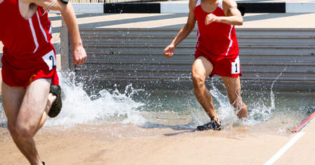 Two runners racing the steeplechase in red uniforms landing and running out of the water competing in a 3000 meter run.