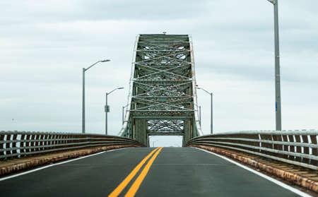 Driving up an empty Robert Moses Bridge from Fire Island New York on a cloudy afternoon