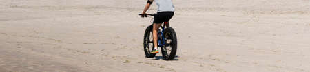 Rear view of a man riding a fat wheel bike on the beach in Fire Island Long Island New York.