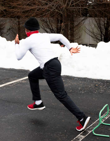 Fast High school track and field sprinter runner running over small hurdles in a parking lot with snow on the side wearing a face mask gaiter.