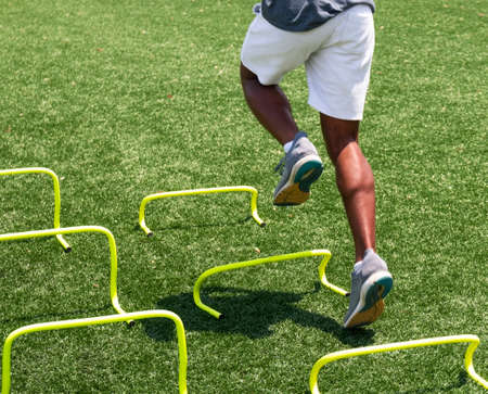 A high school runner is running over yellow mini hurdles at track camp.