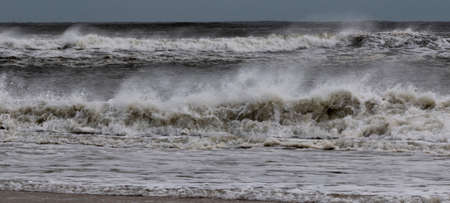 The Atlantic Ocean off the coast of Fire Island New York is very rough with many waves forming from a tropical storm and extraordinarily strong winds blowing the water backwards.)