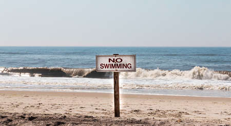 No swimming wood sign at the beach with waves breaking on the shore of Fire Island New York.