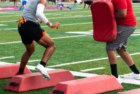 Football player running sideways over red barriers while taking a hit by the coach with a red pad at summer camp