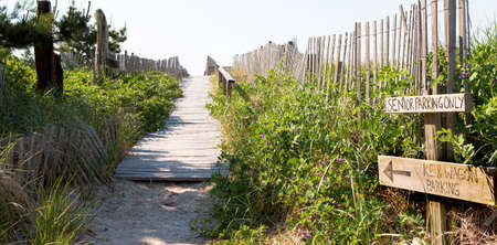 Path from summer homes to the Atlantic Ocean beaches of Fire Island with wood on the sand, hand rails and picket fenceing with green shrubs and wagon parking sign. Stockfoto