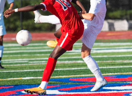 Two high school boys soccer players in a battle for the ball during a game on a turf field.