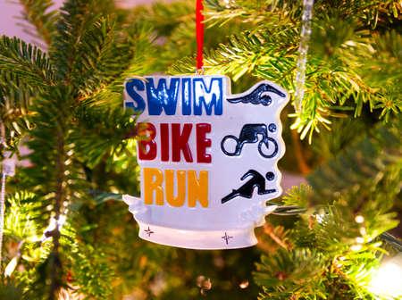 Swim bike run triathlete Christmas ornament hanging on a Christmas tree.