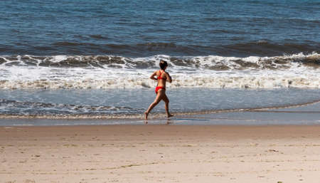 Rear view of a female lifeguard in red bikini running in the ocean water on the edge of the beach. Stockfoto