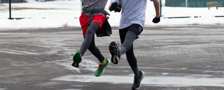 Two high school boy runners bounding in a wet and icy parking lot after a snow storm.