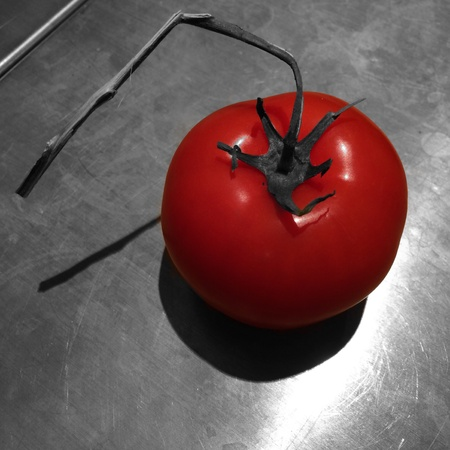 black white red: Red tomato isolated from black and white table
