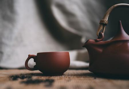 Chinesische Tee-Zeremonie. Brown Tasse Tee und Teekanne auf Bambusmatte
