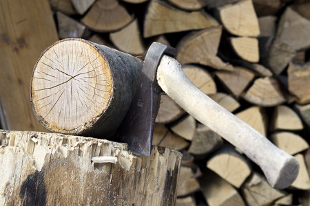 short cut: Short drive ax in a chopping block and nice cut of wood block. Firewood in background Stock Photo