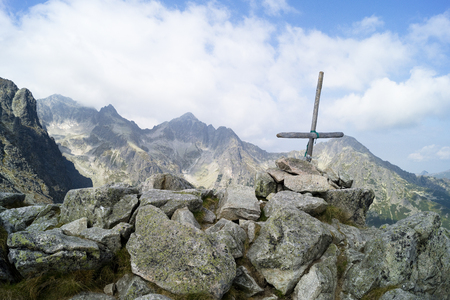 faraway: Tatra Mountains peaks panorama, view from top of the mountain Velka Svistovka. Wooden cross is marking top. Slovakia Stock Photo