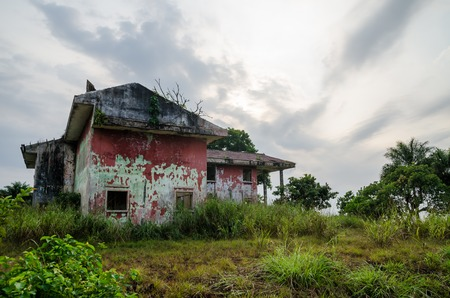 Ruined mansion surrounded by lush green with dramatic sky. Traces of the civil war in Liberia. Stock Photo