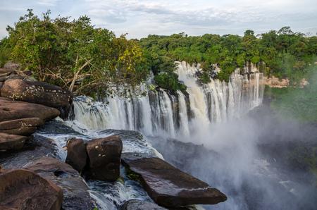緑豊かな緑の熱帯雨林、岩とスプレー フルフローのアンゴラの Kalandula 滝 写真素材