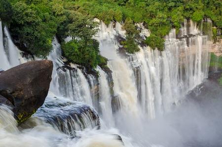 Kalandula waterfalls of Angola in full flow with lush green rain forest, rocks and spray Stock Photo - 67076334