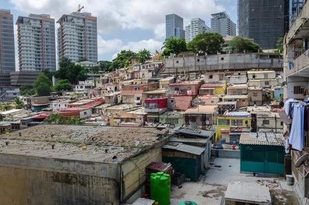 Kleurrijke illegale huizen van de arme inwoners van Luanda, Angola. Deze getto's lijken op Braziliaanse favela's. Op de achtergrond bouwen de hoge gebouwen van de rijken een groot contrast. Stockfoto - 67585813