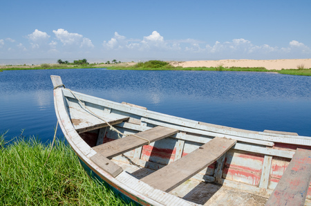 Fishing boat anchored in lagoon with green grass and dunes and clouds in background near Lobito, Angola