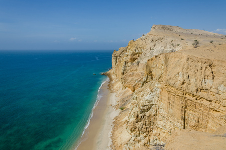 sharply: Impressive cliffs with turquoise ocean at the coast at Caotinha, Angola. The yellow sandstone drops sharply down to the sea here.