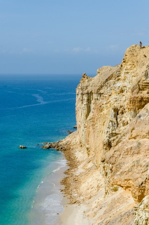 Impressive cliffs with turquoise ocean at the coast at Caotinha, Angola. The yellow sandstone drops sharply down to the sea here.