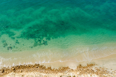 Stark contrast of beautiful turquoise blue ocean meeting yellow beach taken from the cliffs above in Caotinha, Angola. Stock Photo