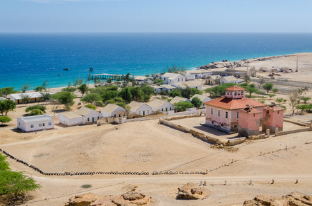 Small fishing village Mucuio with dominating Portuguese colonial building and white washed buildings in Angola.