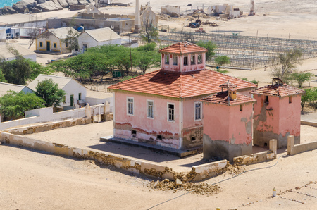 Large pink ruined mansion from Portuguese colonial times in small coastal village of Angolas Namib Desert.