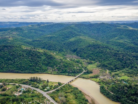 Aerial view of bridge crossing brown river at South Africas Wild Coast near Port St. Johns.