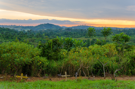 Simple wooden crosses and graves in front of lush jungle and dramatic sunset in Democratic Republic of Congo. Stock Photo