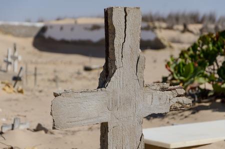 despacio: Abandonado cementerio con cruces y piedras en ruinas en el desierto de Namib de Angola. La arena se está cobrando poco a poco el sitio de nuevo y que parece olvidado y abandonado.