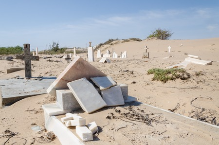 Abandoned graveyard with crumbling stones and crosses in Namib Desert of Angola. The sand is slowly claiming the site back and it seems forgotten and abandoned. Stock Photo