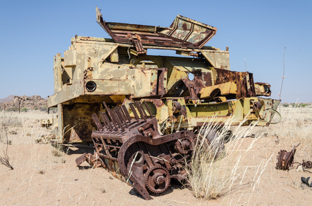 dismantled: Abandoned harvester rusting away deep in the Namib Desert of Angola with fence in background.