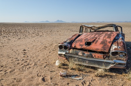 Wreck of classic saloon car abandoned deep in the Namib Desert of Angola. What caused the accident and what happened to the travelers remains a mystery. Stock Photo