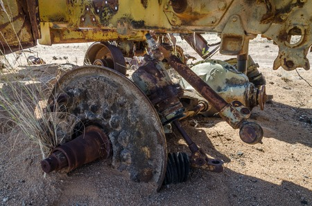 axle: Massive axle of abandoned harvester rusting away deep in the Namib Desert of Angola in detail.
