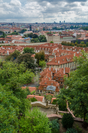 Aerial or rock view over the historical city of Prague in Czech Republic on an overcast early autumn day. The many red tiled roofs and beautifully kept old building stick out. Stock Photo