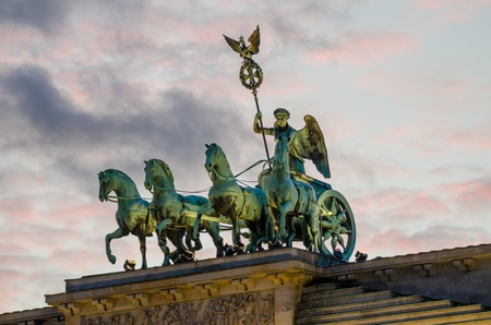 quadriga: Detail of sculptures on top of Brandenburger Tor in Berlin with pink evening light and soft clouds, Germany