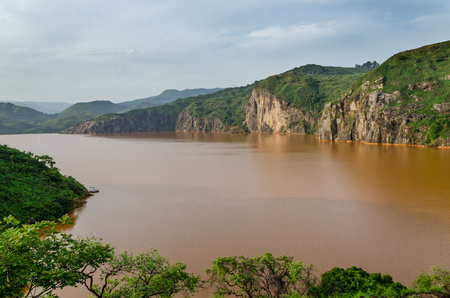Landscape including calm brown water of Lake Nyos, famous for CO2 eruption with many deaths, Ring Road, Cameroon Reklamní fotografie
