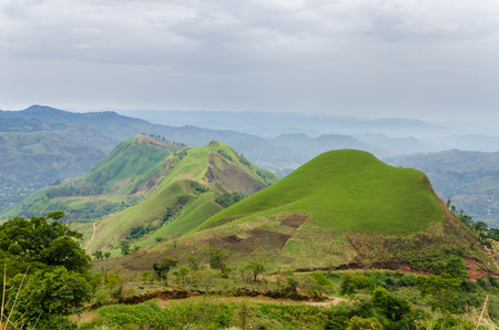 Rolling fertile hills with fields and crops on Ring Road of Cameroon, Africa