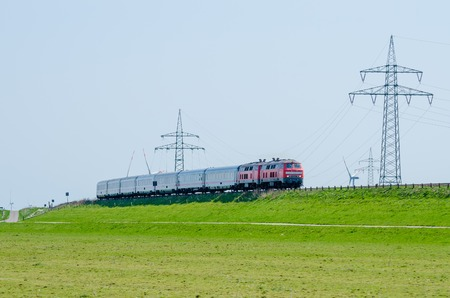 German train driving on Hindenburg Dam towards the island Sylt with green grass and electricity poles, Germany