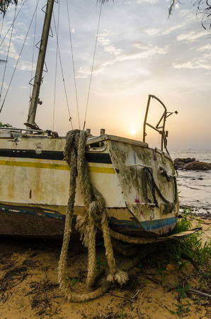 Abandoned sailing boat or yacht laying on beach in Kribi, Cameroon during sunset, Africa Stock Photo