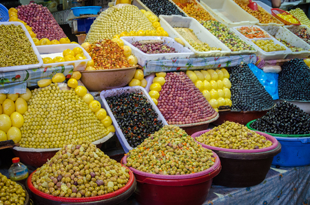 Large amounts of pyramidically stacked olives for sale on market or soukh of Marrakesh, Morocco