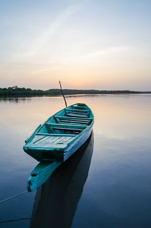 Beautiful wooden fishing boat on Gambia river during blue hour in the evening, The Gambia, West Africa