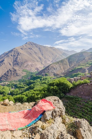 View on beautiful High Atlas Mountains landscape with lush green valley, rocky peaks and red carpet, Morocco, Africa