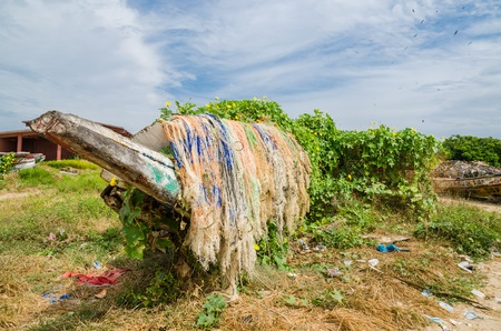 tradition: Colorful overgrown and broken wooden fishing boats with nets and traps in lush environment, coast of Gambia, West Africa