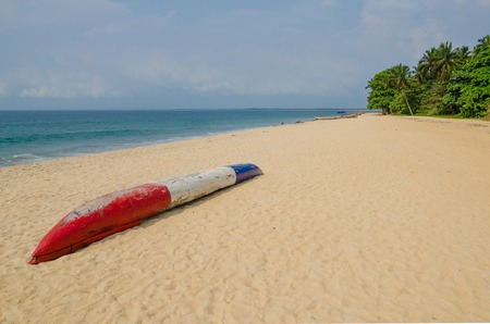 Colorful dugout fishing boat laying on deserted tropical beach at Robertsport, Liberia, West Africa Stock Photo - 87602814