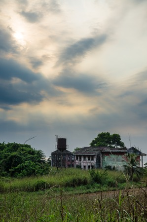 Ruined mansion surrounded by lush green with dramatic sky. Traces of the civil war in Robertsport, Liberia Stock Photo
