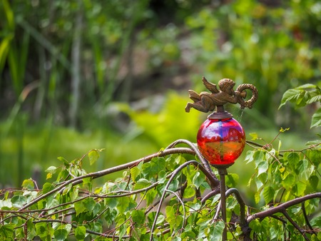 Red seethrough glass ball on rusty stick with decorative angel and reflection of house, garden in Germany Stock Photo